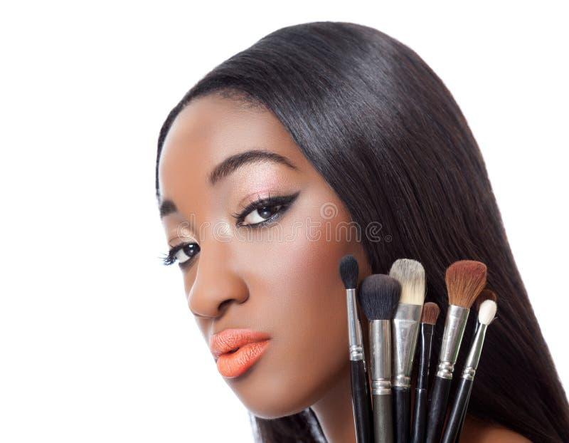 Femme de couleur avec les cheveux droits tenant des brosses de maquillage photo libre de droits