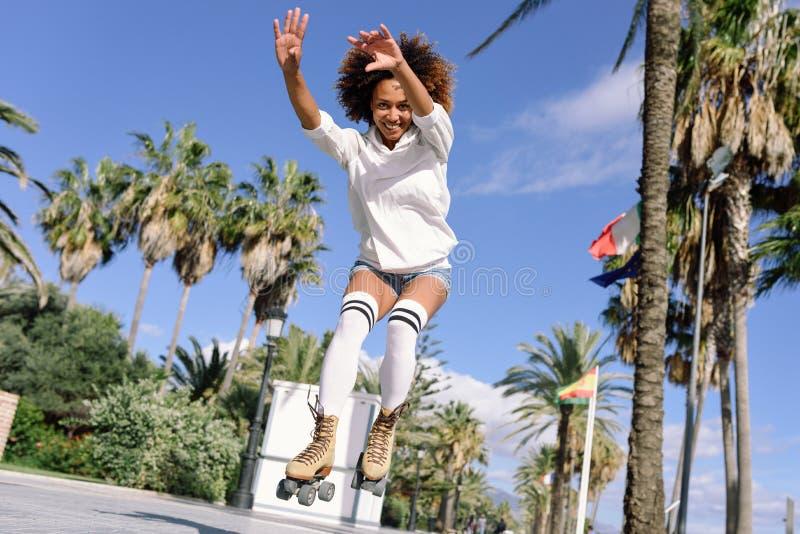 Femme de couleur, coiffure Afro, sur des patins de rouleau sautant près du b photographie stock