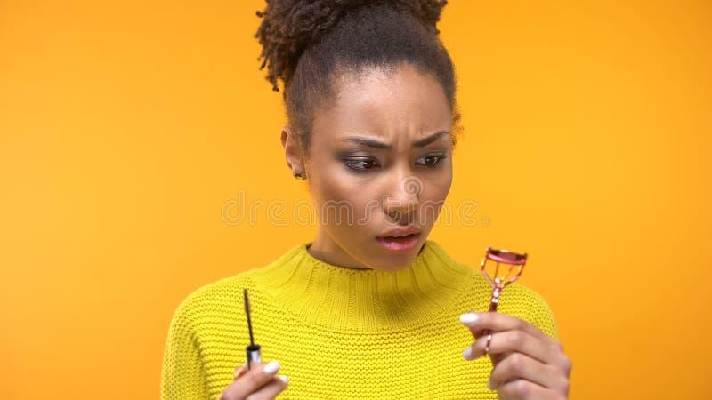 Femme de couleur confuse regardant le bigoudi de mascara et de cil, astuces de maquillage, beauté images libres de droits