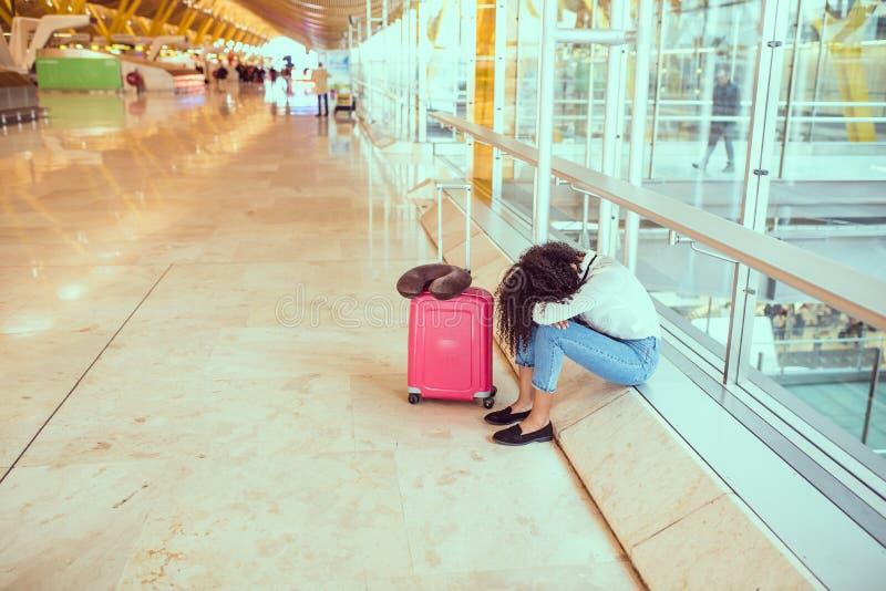 Femme de couleur contrariée et frustrée à l'aéroport avec le canc de vol photo libre de droits