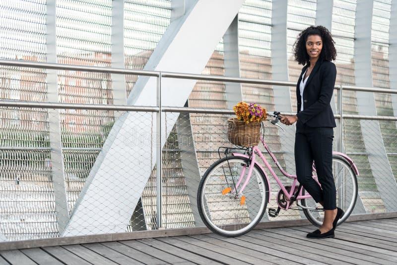 Femme de couleur d'affaires avec la bicyclette de vintage dans un pont images libres de droits