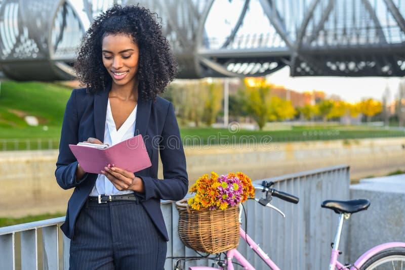 Femme de couleur d'affaires avec la bicyclette de vintage par la rivière regardant a photos libres de droits