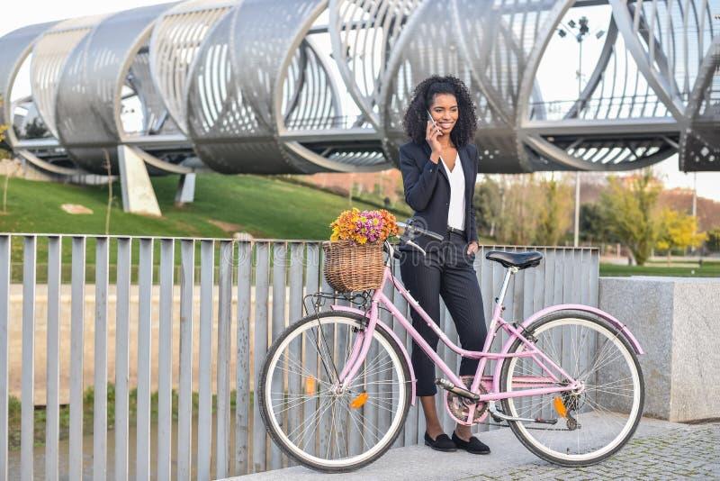 Femme de couleur d'affaires se tenant prêt sa bicyclette de vintage parlant dessus image libre de droits
