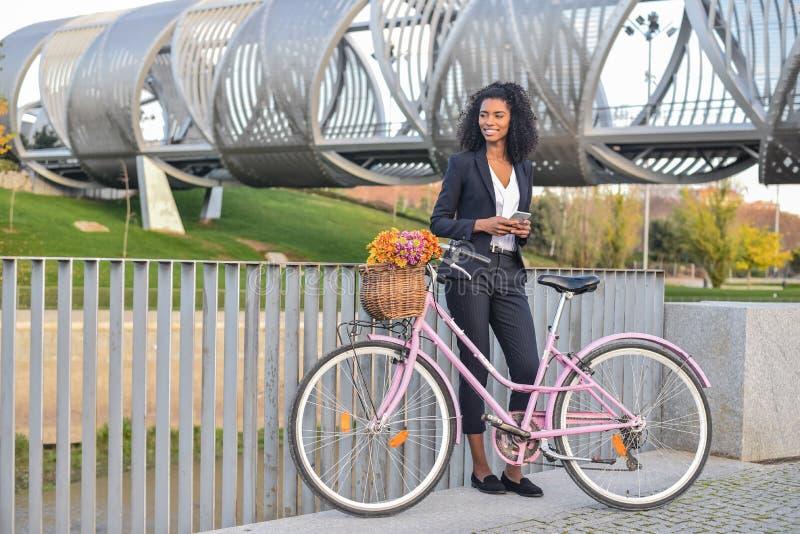 Femme de couleur d'affaires se tenant prêt sa bicyclette de vintage parlant dessus image stock