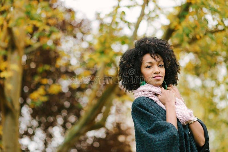 Femme de couleur dans le jour froid d'automne au parc photographie stock