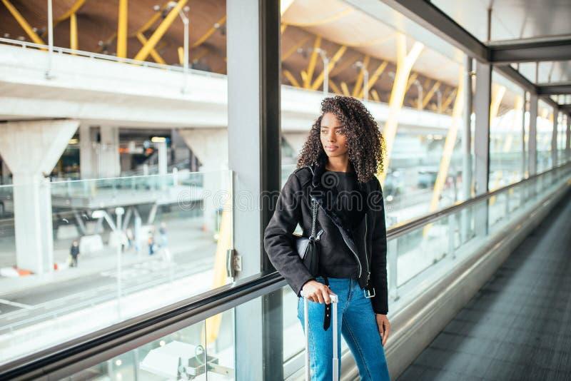 Femme de couleur dans le passage couvert mobile à l'aéroport avec un Sui rose images libres de droits