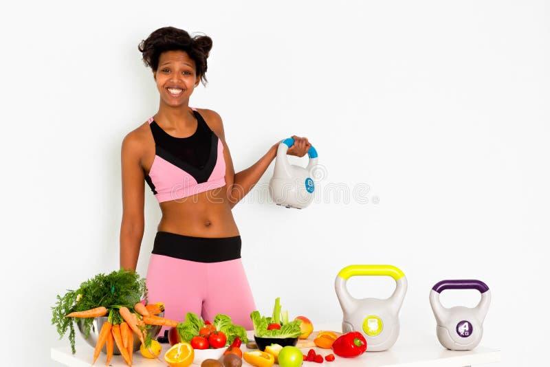Femme de couleur folâtre de forme physique, formation à la maison de femme de couleur de forme physique avec des poids images stock