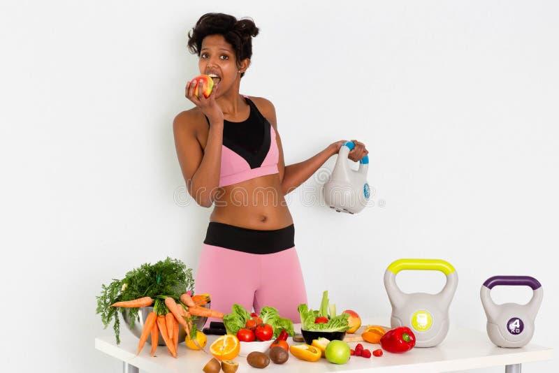 Femme de couleur folâtre de forme physique, formation à la maison de femme de couleur de forme physique avec des poids images libres de droits