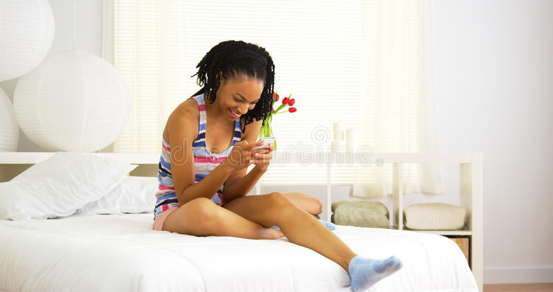 Femme de couleur mignonne s'asseyant sur le service de mini-messages de lit photo stock