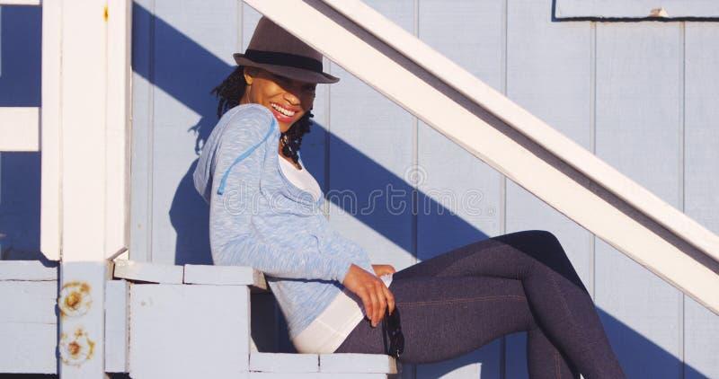 Femme de couleur mignonne s'asseyant sur les escaliers extérieurs photographie stock libre de droits