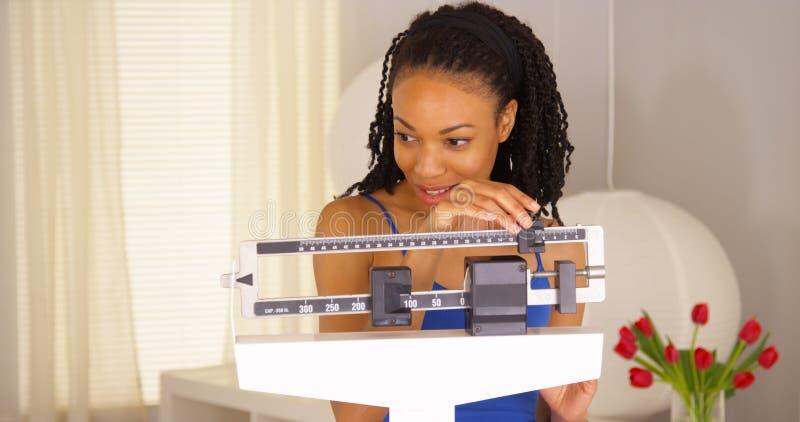 Femme de couleur mignonne souriant sur des échelles images libres de droits
