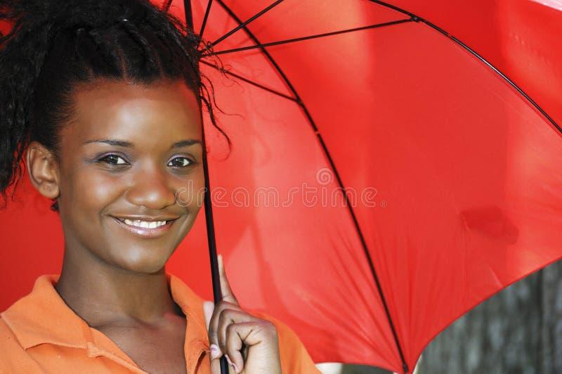 Femme de couleur retenant un parapluie images stock