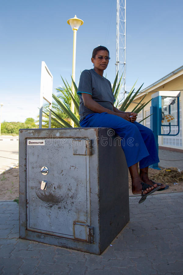 Femme de couleur s'asseyant sur une banque plus sûre à la frontière namibienne en BO photo stock