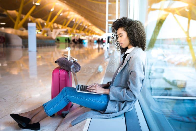 Femme de couleur travaillant avec l'ordinateur portable à l'aéroport attendant aux WI photographie stock