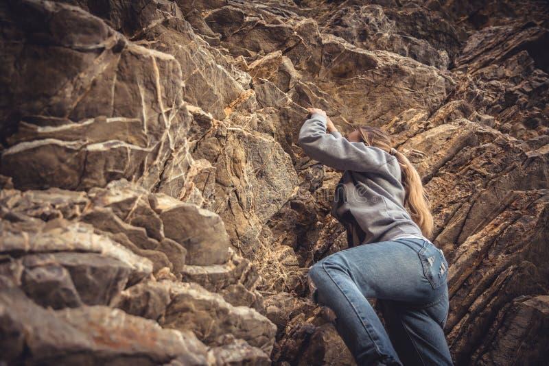 Femme de courage atteignant son but s'élevant sur la roche photographie stock libre de droits