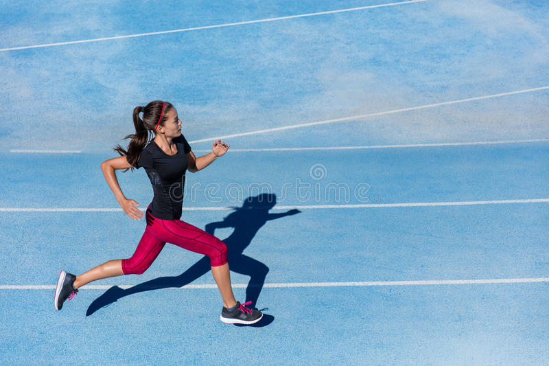Femme de coureur d'athlète courant sur la voie sportive de course image libre de droits