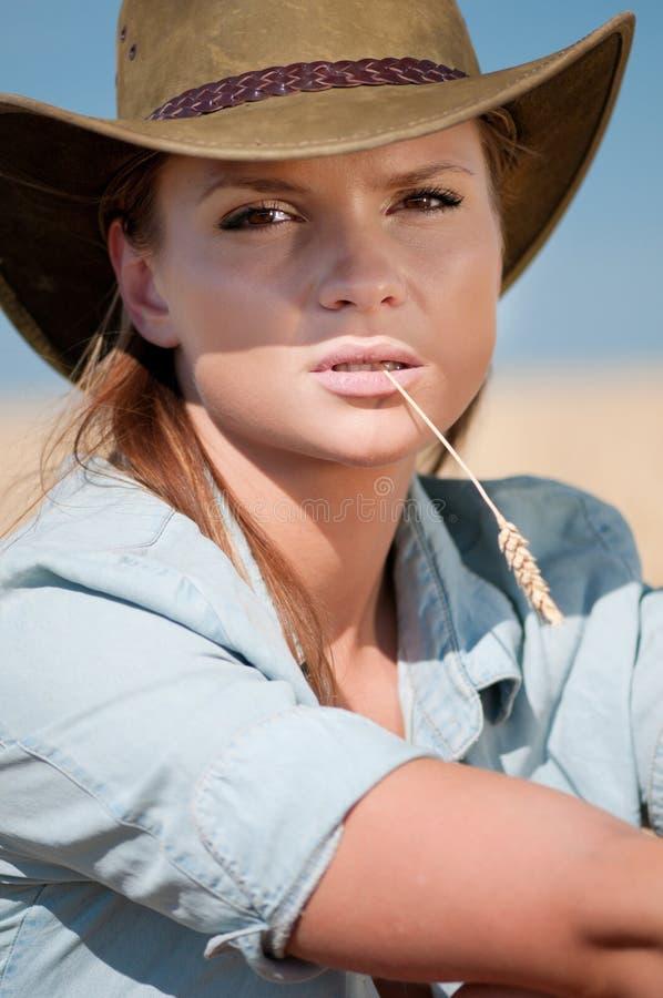 Femme de cowboy dans le domaine de blé de pays photos stock