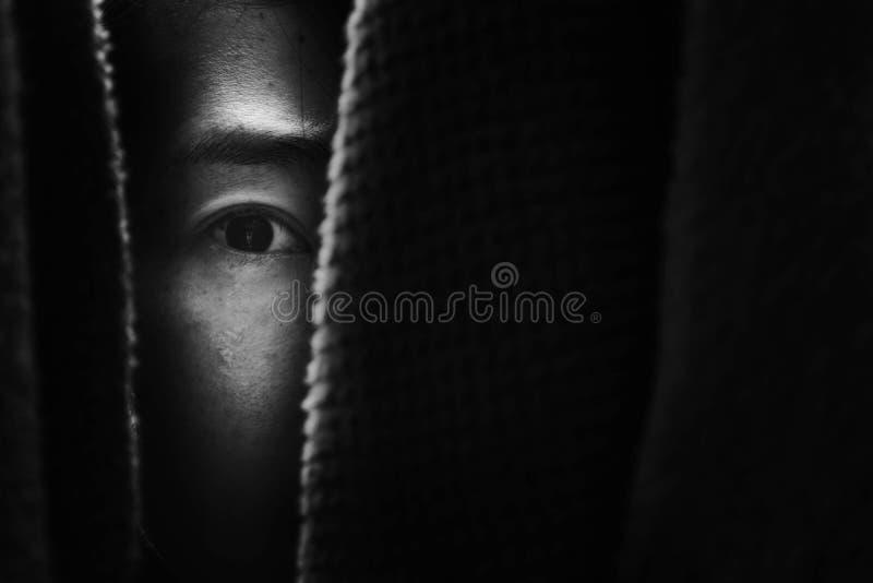 Femme de crainte se cachant dans le cabinet photo stock