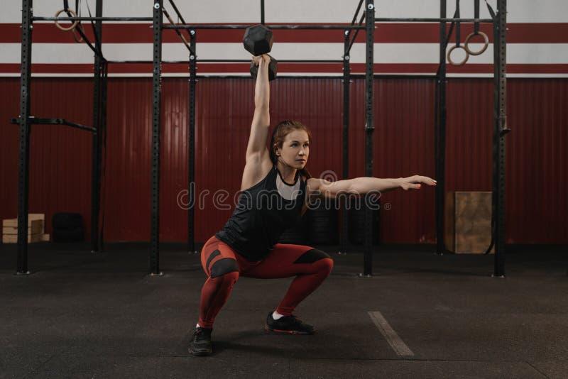 Femme de Crossfit faisant des postures accroupies aériennes d'haltère au gymnase images libres de droits