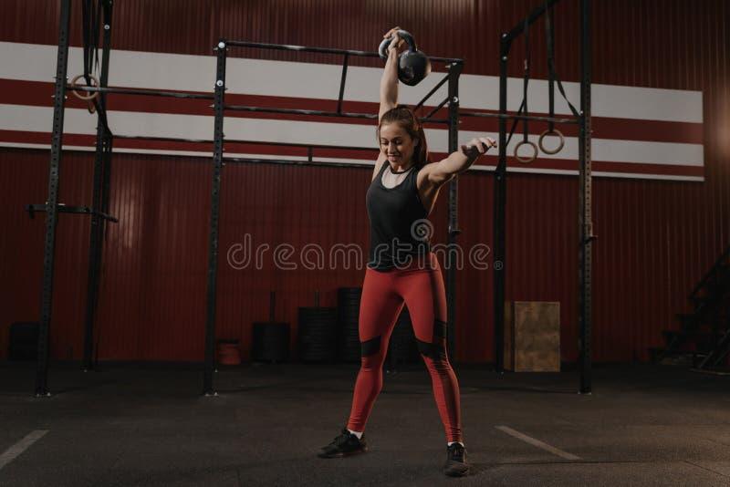 Femme de Crossfit jugeant un kettlebell formation aérienne et souriante de crossfit de moment au gymnase photographie stock libre de droits