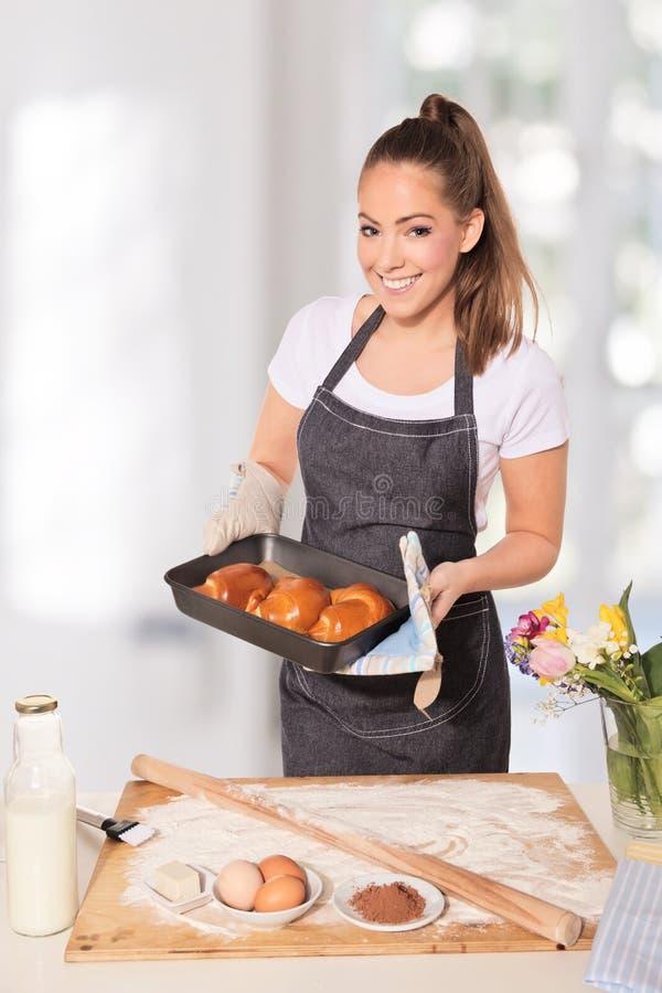 Femme de cuisson montrant un plateau des biscuits frais hors du four photographie stock