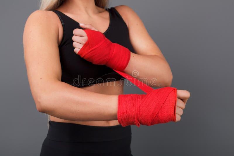 Femme de culture mettant des gants de boxeur photos stock