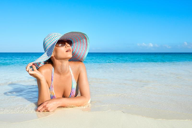 Femme de détente dans le bikini et le chapeau d'été appréciant le soleil d'été photographie stock libre de droits