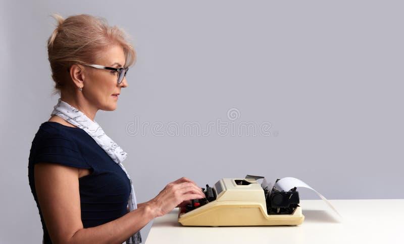 Femme de dactylo avec la machine à écrire D'isolement image libre de droits