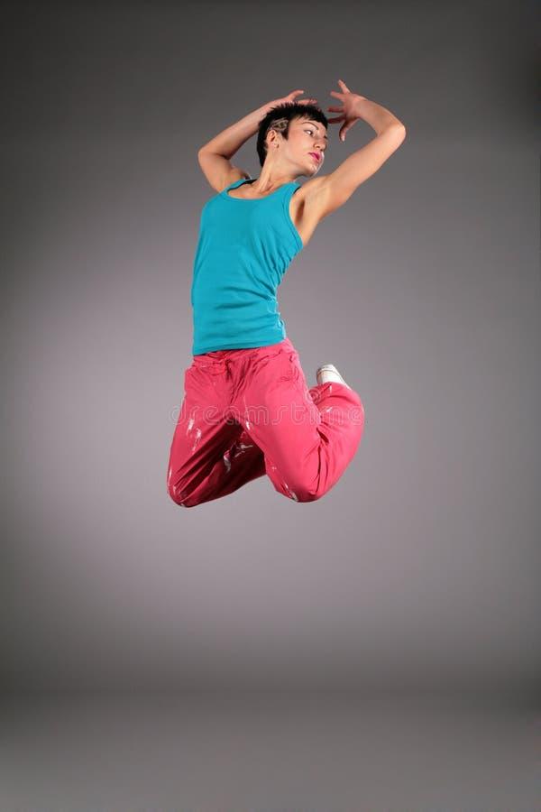 Femme de danse dans des sauts de vêtements de sport photographie stock libre de droits