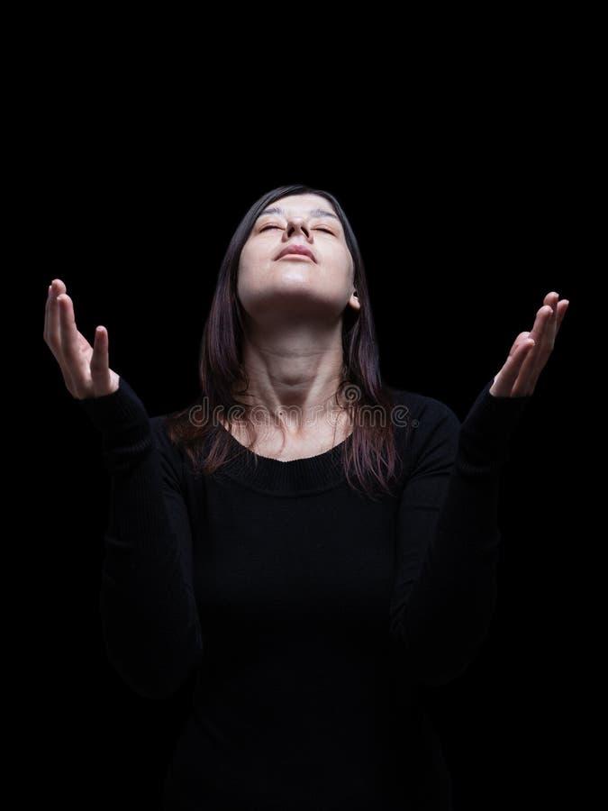 Femme de deuil priant, avec des bras tendus dans le culte à un dieu photos stock
