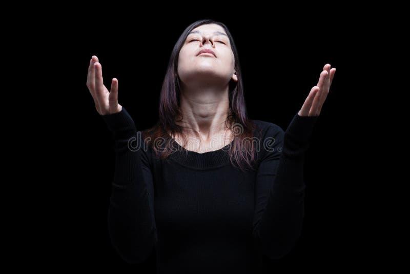 Femme de deuil priant, avec des bras tendus dans le culte à un dieu image libre de droits