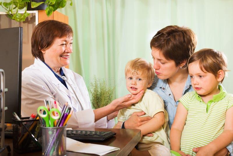 Femme de deux enfants parlant avec le docteur amical photographie stock