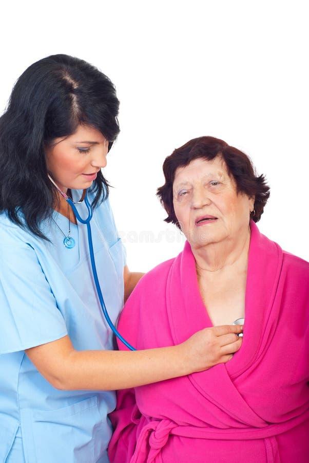 Femme de docteur évaluant le vieux patient images libres de droits