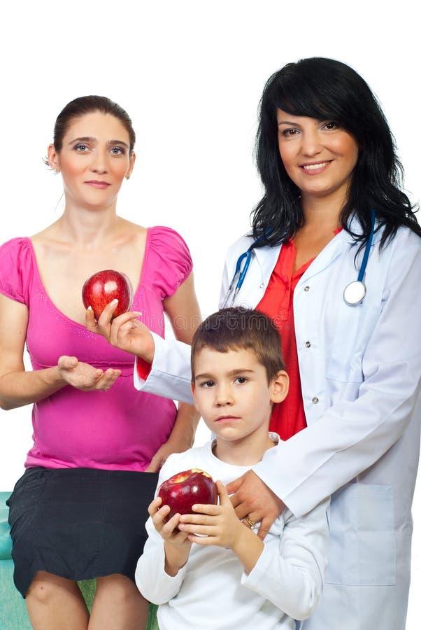 Femme de docteur donnant des pommes à un famille photographie stock libre de droits