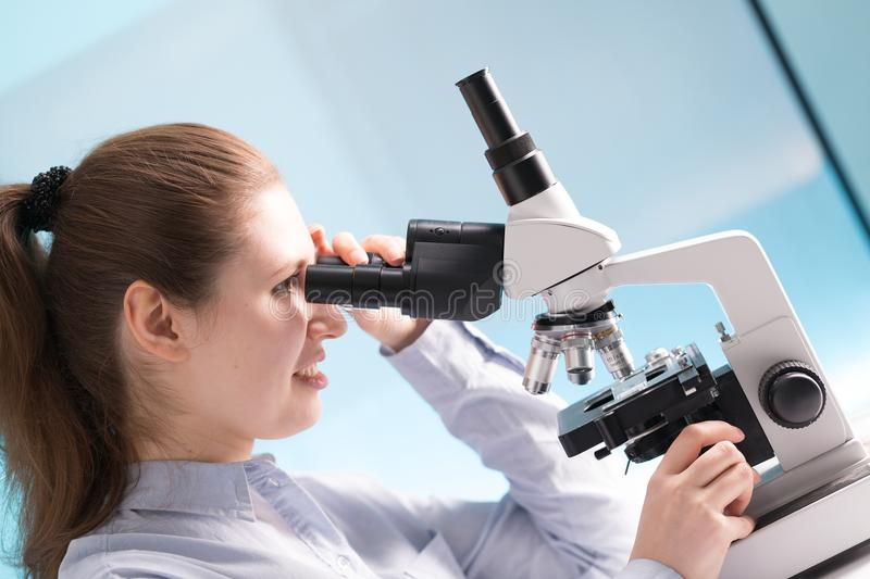 Femme de docteur travaillant un microscope Scientifique féminin regardant le thr photo libre de droits