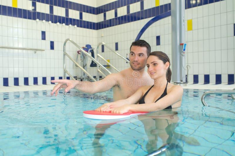 Femme de enseignement d'homme à nager photos stock