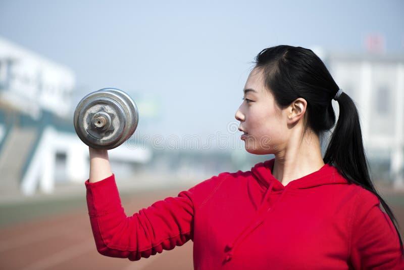 Femme de forme physique établissant avec l'haltère image stock