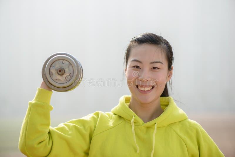 Femme de forme physique établissant avec l'haltère image libre de droits