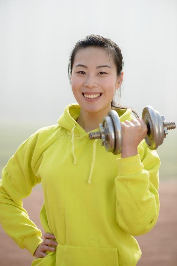 Femme de forme physique établissant avec l'haltère photographie stock libre de droits