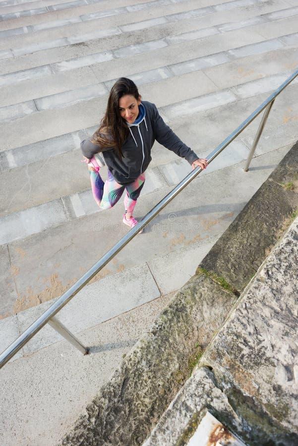 Femme de forme physique étirant des jambes avant séance d'entraînement urbaine photo stock