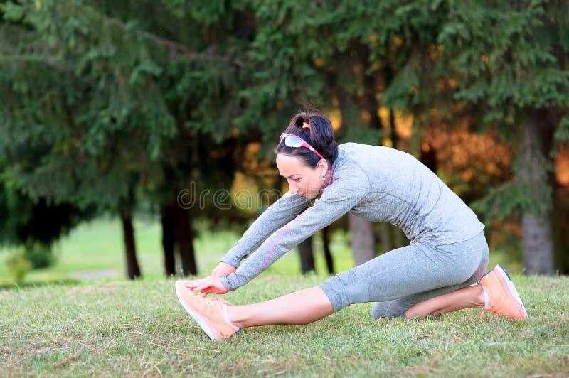Femme de forme physique étirant sa jambe pour réchauffer dehors photographie stock