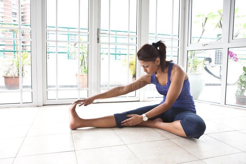 Femme de forme physique étirant son tendon du jarret photographie stock