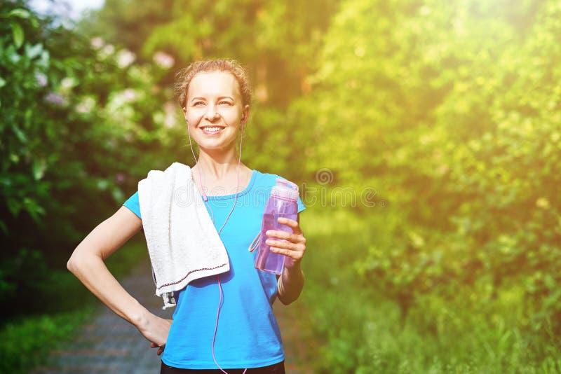 Femme de forme physique avec la bouteille et la serviette de l'eau après la formation courante en parc d'été image libre de droits