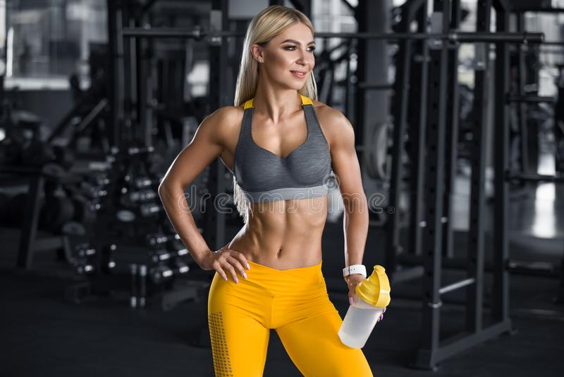 Femme de forme physique avec le dispositif trembleur dans le gymnase, eau potable  Fille sportive, taille abdominale et mince for photographie stock libre de droits