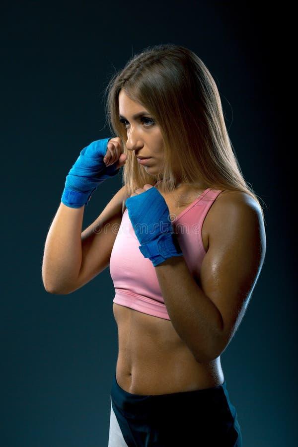 Femme de forme physique avec les bandages bleus de boxe, tir de studio image stock