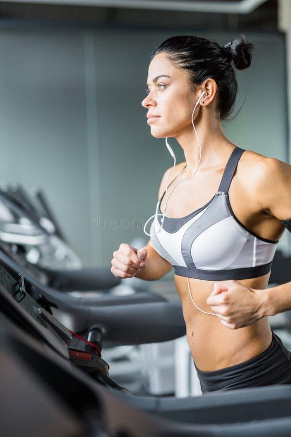 Femme de forme physique courant sur le tapis roulant pendant la séance d'entraînement dans le gymnase photo stock