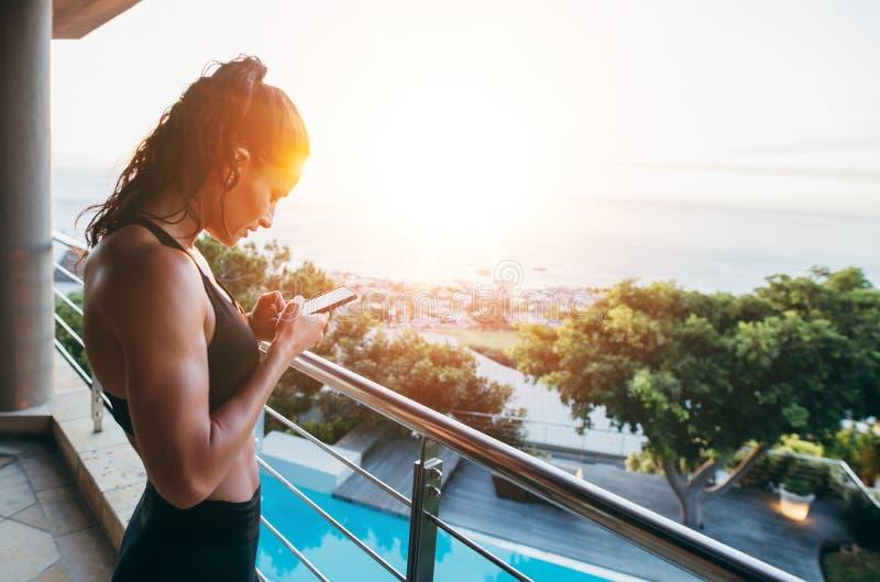 Femme de forme physique dans le balcon utilisant le téléphone portable image libre de droits