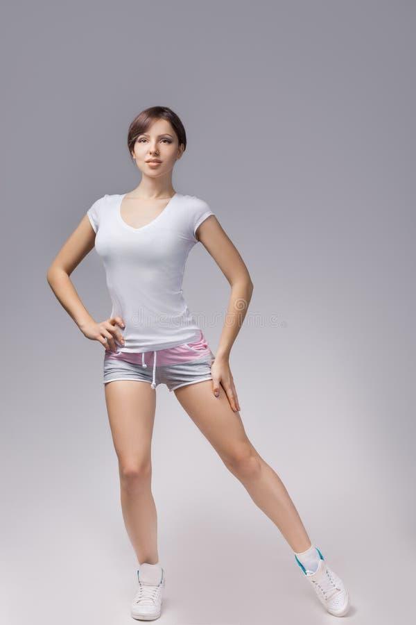 Femme de forme physique dans le style de sport se tenant sur le fond blanc D'isolement photographie stock libre de droits