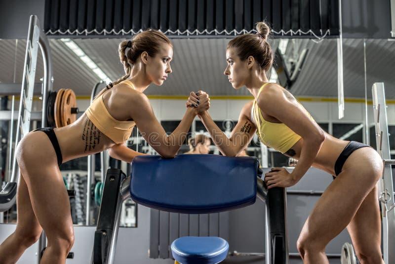 Femme de forme physique de deux jeunes, bras de fer dans le gymnase photo libre de droits