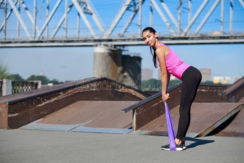 Femme de forme physique faisant étirant des exercices avec une bande élastique élastique sur le fond urbain de ville photos libres de droits